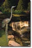 Outdoor garden lights being use to light a crane and waterfall feature.