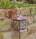 Picture of a hanging copper solar light mounted to the side of a rock wall.